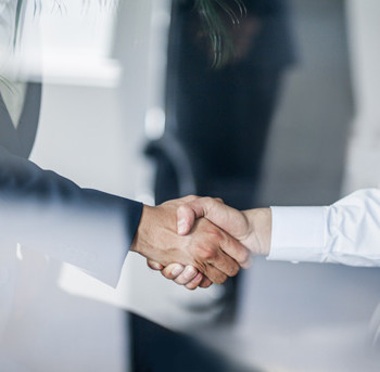 Business handshake in glass reflection in office